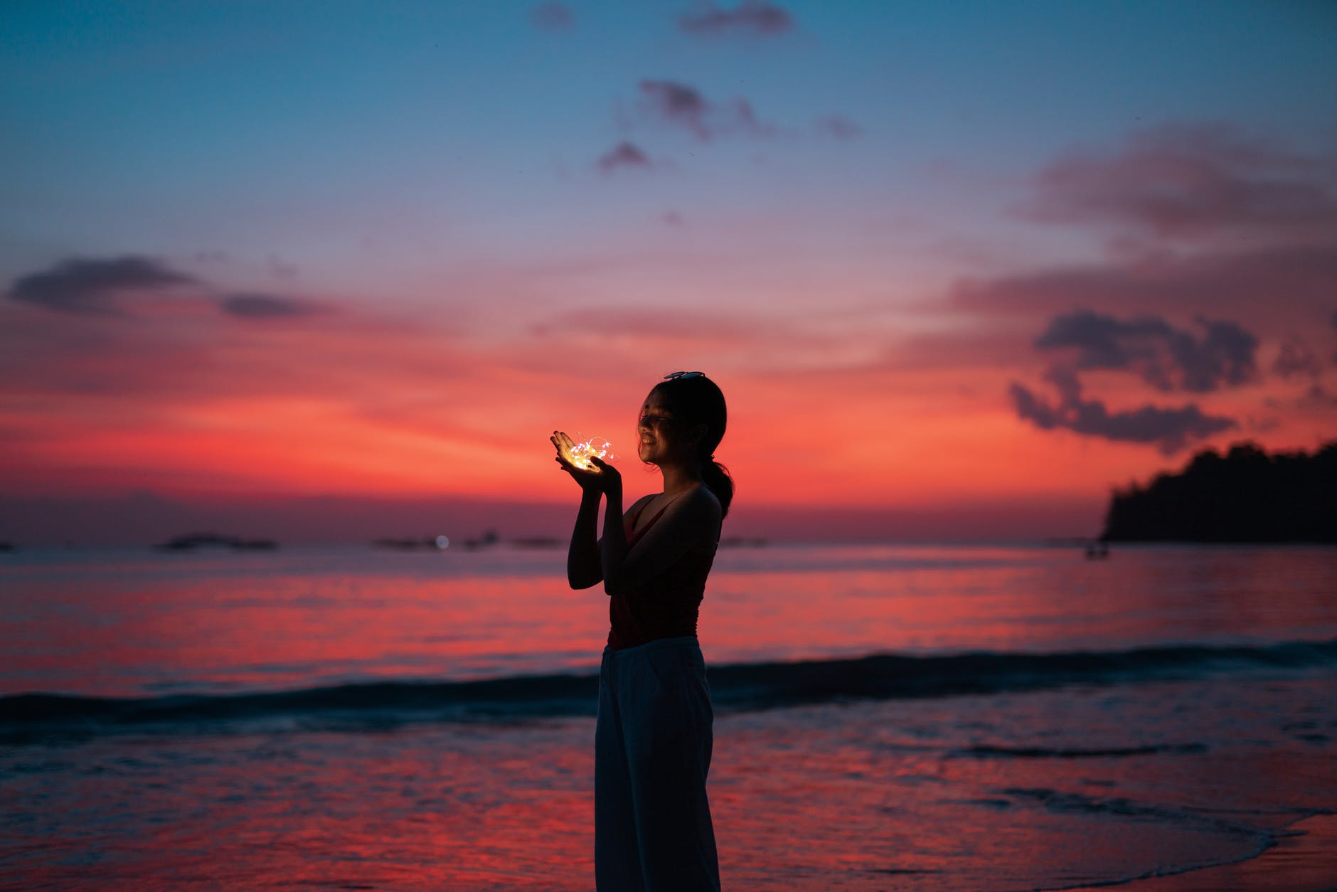 woman holding lights on seashore at sunset